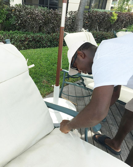 Franklyn Bain, pool and beach supervisor meticulously sets the cushions around the pool.