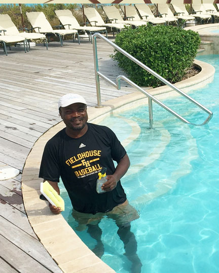 Eddy Joseph, pool and beach attendant is making sure those pool tiles in the main pool are sparkling!