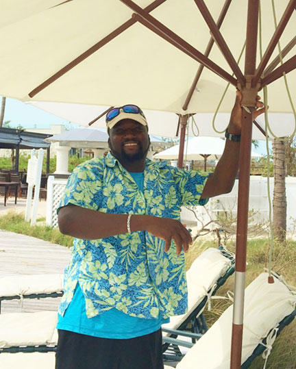 Delroy McIntosh exudes so much pride and joy as he tests the umbrellas around the pool.